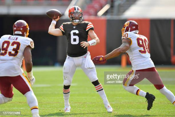 Quarterback Baker Mayfield of the Cleveland Browns passes while under pressure from defensive tackle Jonathan Allen and defensive end Montez Sweat of...
