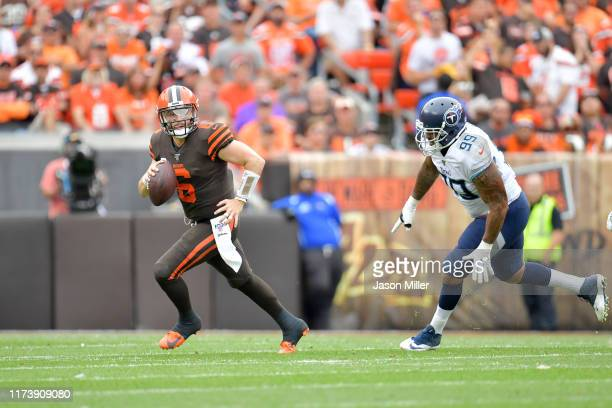 Quarterback Baker Mayfield of the Cleveland Browns scrambles out of the pocket while under pressure from defensive end Jurrell Casey of the Tennessee...