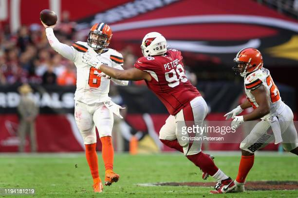 Quarterback Baker Mayfield of the Cleveland Browns throws a pass under pressure from defensive tackle Corey Peters of the Arizona Cardinals during...
