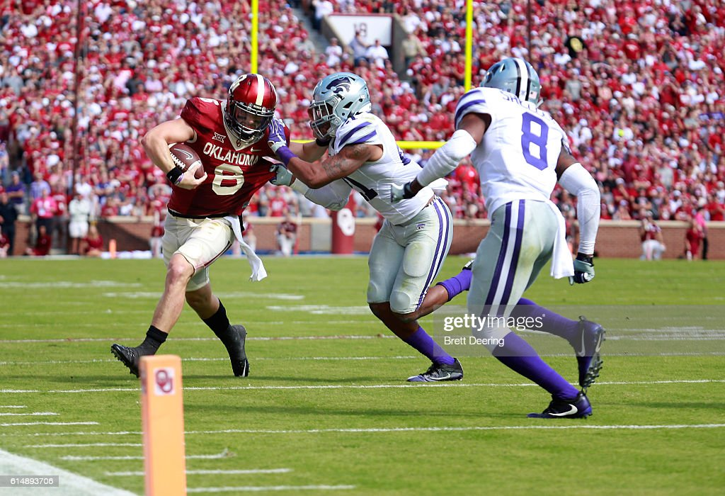 Quarterback Baker Mayfield #6 of the Oklahoma Sooners is hit by defensive back Kendall Adams #21 of the Kansas State Wildcats October 15, 2016 at Gaylord Family-Oklahoma Memorial Stadium in Norman, Oklahoma. Oklahoma defeated Kansas State 38-17.