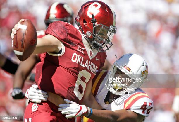 Quarterback Baker Mayfield of the Oklahoma Sooners is hit by linebacker Marcel Spears Jr #42 of the Iowa State Cyclones at Gaylord Family Oklahoma...