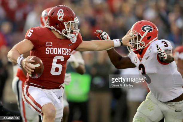 Quarterback Baker Mayfield of the Oklahoma Sooners looks to avoid a sack by linebacker Roquan Smith of the Georgia Bulldogs in the second half in the...