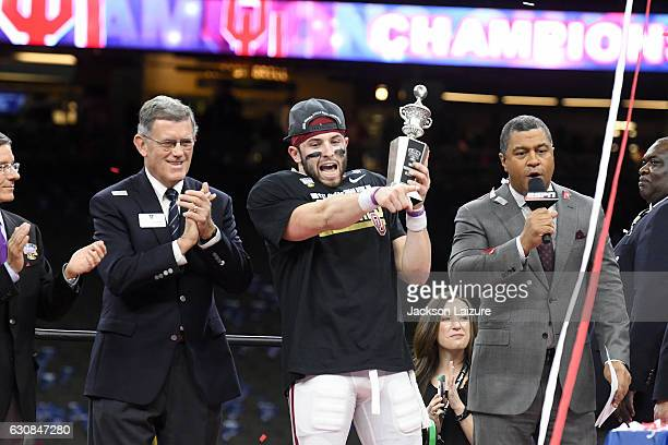 Quarterback Baker Mayfield of the Oklahoma Sooners receives the most outstanding player trophy after their victory against the Auburn Tigers in the...