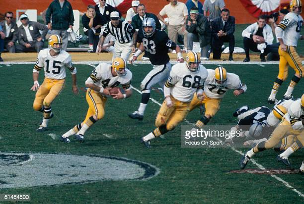 Quarterback Bart Starr of the Green Bay Packers hands the ball off to Donny Anderson against the Oakland Raiders defense during Super Bowl II in...