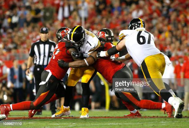 Quarterback Ben Roethlisberger of the Pittsburgh Steelers is sacked by defensive end Vinny Curry of the Tampa Bay Buccaneers and defensive tackle...