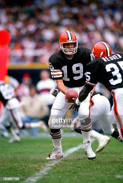 Quarterback Bernie Kosar of the Cleveland Brown turns to hand the ball off to Barry Redden during an NFL football game at Cleveland Municipal Stadium...