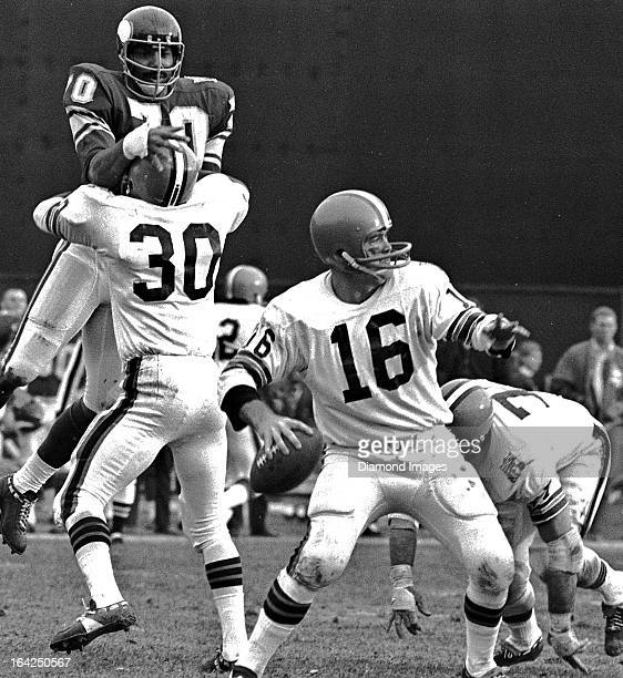 Quarterback Bill Nelsen of the Cleveland Browns throws a pass while running back Ron Johnson blocks defensive end Jim Marshall of the Minnesota...