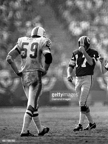 Quarterback Billy Kilmer of the Washington Redskins and Doug Swift of the Miami Dolphins walk off the field to their respective sidelines during...