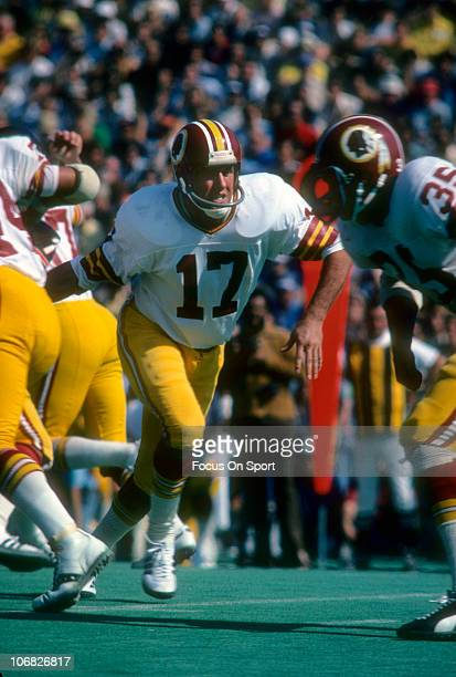 Quarterback Billy Kilmer of the Washington Redskins hands the ball off to a running back against the Chicago Bears during an NFL football game at...
