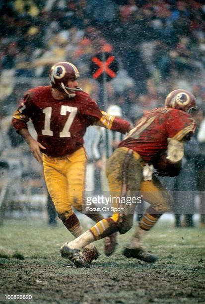 Quarterback Billy Kilmer of the Washington Redskins hands the ball off to Charlie Harraway against the Philadelphia Eagles during an NFL football...