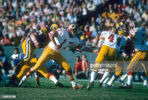 Quarterback Billy Kilmer of the Washington Redskins turns and hand the ball off to Moses Denson against the Los Angeles Rams during an NFL football...