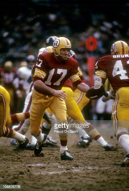 Quarterback Billy Kilmer of the Washington Redskins turns to hand the ball off to running back Larry Brown against the New York Giants during an NFL...
