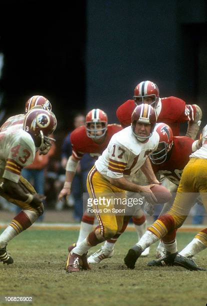 Quarterback Billy Kilmer of the Washington Redskins turns to hand the ball off to Larry Brown against the Atlanta Falcons during an NFL football game...