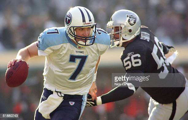 Quarterback Billy Volek of the Tennessee Titans evades the sack attempt from linebacker Travian Smith of the Raiders on December 19 2004 at Network...