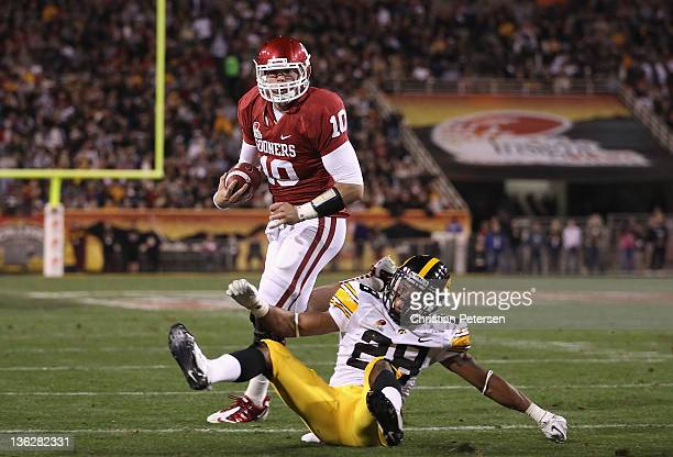 Quarterback Blake Bell of the Oklahoma Sooners scores on a 4 yard rushing touchdown past defensive back Shaun Prater the Iowa Hawkeyes during the...