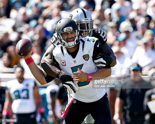 Quarterback Blake Bortles of the Jacksonville Jaguars is tackled from behind by Linebacker Bruce Irvin of the Oakland Raiders during the game at...