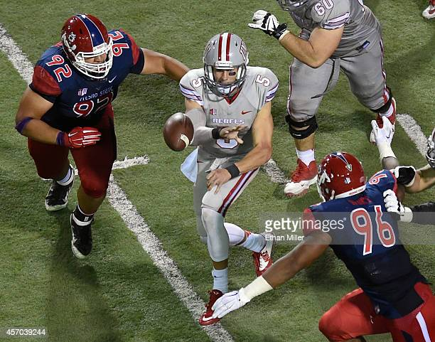Quarterback Blake Decker of the UNLV Rebels passes under pressure from Tyeler Davison and Todd Hunt of the Fresno State Bulldogs during their game at...