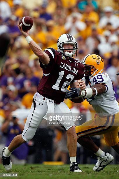 Quarterback Blake Mitchell of the South Carolina Gamecocks throws under pressure from Kirston Pittman of the Louisiana State University Tigers at...