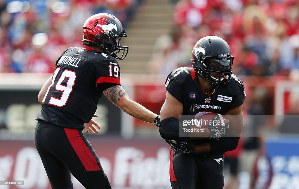 Quarterback Bo Levi Mitchell #19 hands the ball off to Jon Cornish #9 of the Calgary Stampeders against the Edmonton Eskimos in the first half of their CFL football game September 1, 2014 at McMahon Stadium in Calgary, Alberta, Canada.