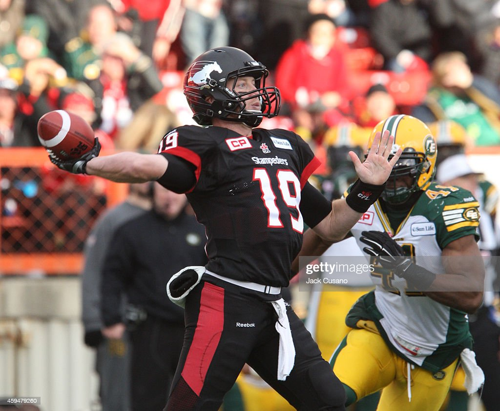 Quarterback Bo Levi Mitchell #19 of the Calgary Stampeders throws a touchdown pass as Adam Thibault #41 of the Edmonton Eskimos rushes him during the divisional finals at McMahon Stadium on November 23, 2014 in Calgary, Alberta, Canada.