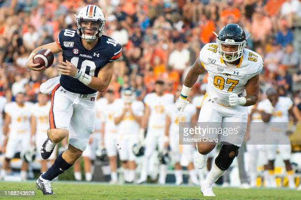 Quarterback Bo Nix of the Auburn Tigers at JordanHare Stadium scrambles with the ball in front of defensive end Zayin West of the Kent State Golden...