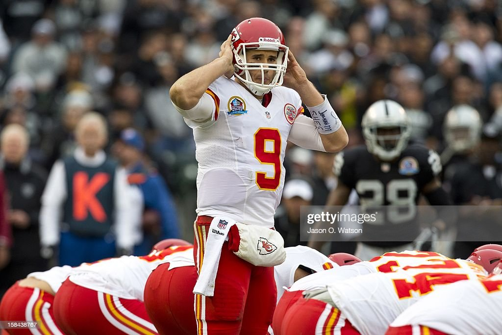 Quarterback Brady Quinn #9 of the Kansas City Chiefs stands behind the line of scrimmage before a play showing an arm band with a bible verse and S.H.E.S. written on it in support of the victims of the Sandy Hook Elementary School shooting during the second quarter against the Oakland Raiders at O.co Coliseum on December 16, 2012 in Oakland, California.