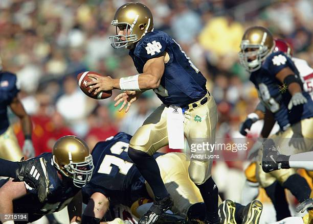 Quarterback Brady Quinn of the Notre Dame Fighting Irish hands the ball off against the USC Trojans on October 18, 2003 at Notre Dame Stadium in...