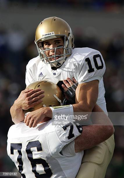 Quarterback Brady Quinn of the Notre Dame Fighting Irish jumps into the arms of lineman Bob Morton after throwing a touchdown against the Air Force...