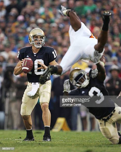 Quarterback Brady Quinn of the Notre Dame Fighting Irish looks for a receiver as teammate Darius Walker blocks and flips Kevin Simon of the...