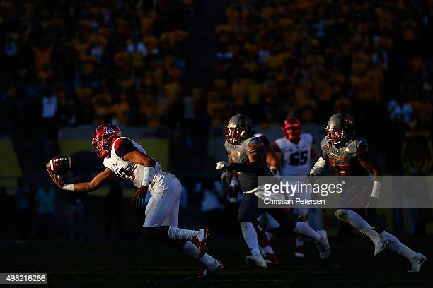 Quarterback Brandon Dawkins of the Arizona Wildcats fumbles the football off the snap during the fourth quarter of the college football game against...