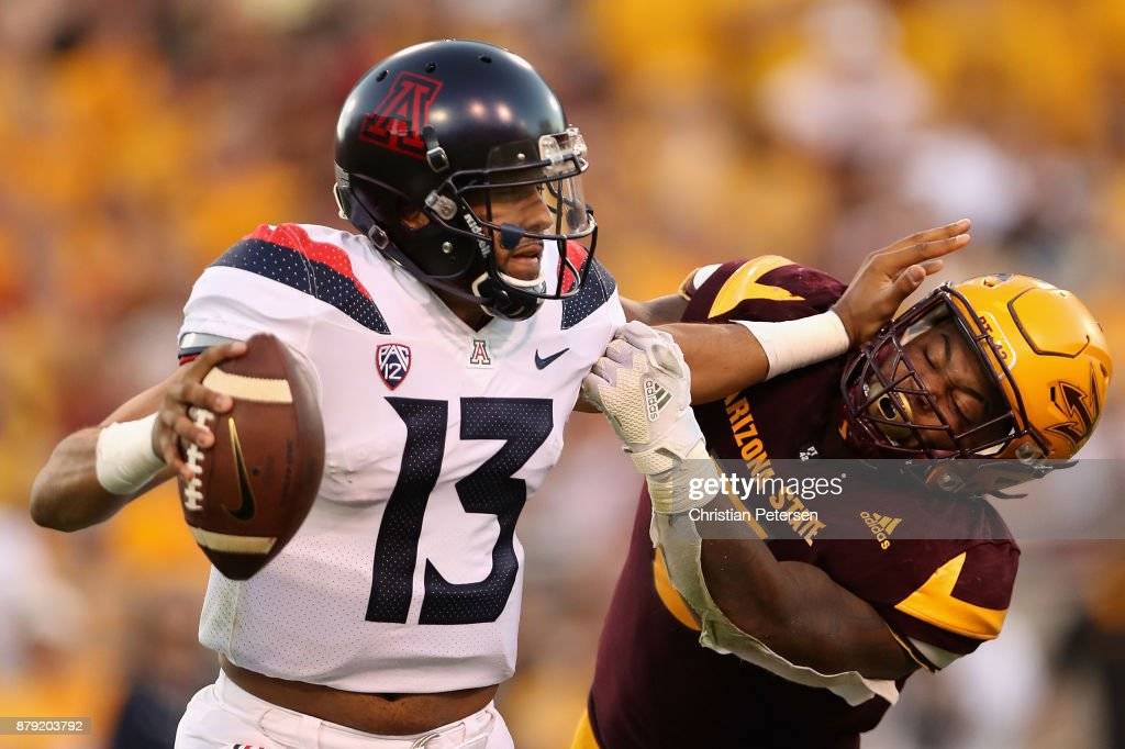 Quarterback Brandon Dawkins #13 of the Arizona Wildcats is sacked by linebacker Christian Sam #2 of the Arizona State Sun Devils during the second half of the college football game at Sun Devil Stadium on November 25, 2017 in Tempe, Arizona. The Sun Devils defeated the Wildcats 42-30.