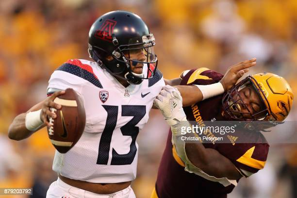 Quarterback Brandon Dawkins of the Arizona Wildcats is sacked by linebacker Christian Sam of the Arizona State Sun Devils during the second half of...