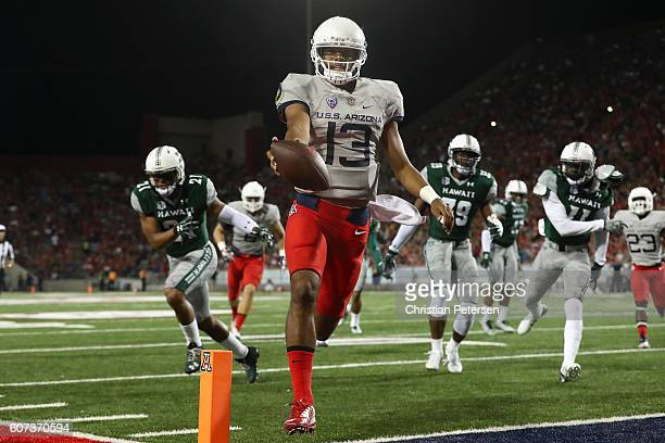 Quarterback Brandon Dawkins of the Arizona Wildcats scores on a 14 yard rushing touchdown against the Hawaii Warriors during the first quarter of the...