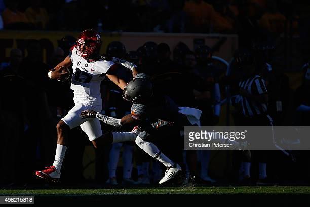 Quarterback Brandon Dawkins of the Arizona Wildcats scrambles with the football past defensive back Solomon Means of the Arizona State Sun Devils...