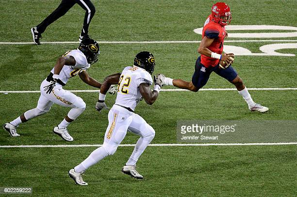 Quarterback Brandon Dawkins of the Arizona Wildcats scrambles with the football in front of linebacker Marchael Jackson and defensive lineman Samuel...