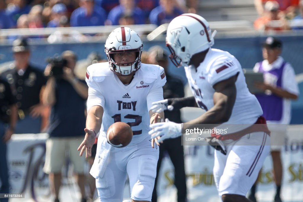 Quarterback Brandon Silvers #12 tosses the ball to running back Jamarius Henderson #9 of the Troy Trojans during first half action against the Boise State Broncos on September 2, 2017 at Albertsons Stadium in Boise, Idaho.