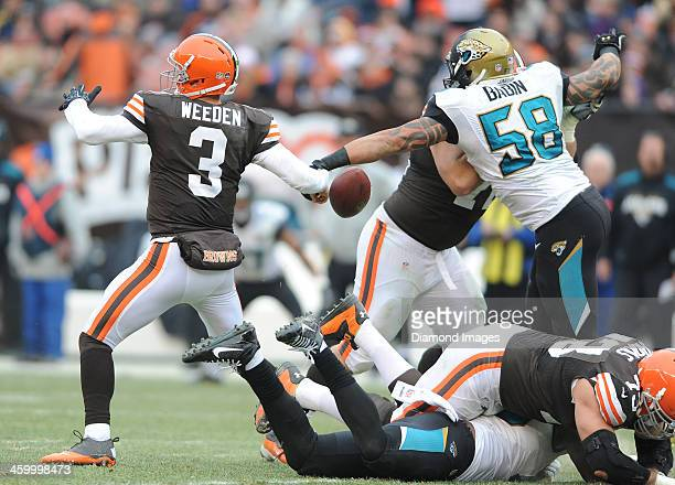 Quarterback Brandon Weeden of the Cleveland Browns fumbles the football while being hit by defensive end Jason Babin of the Jacksonville Jaguars...