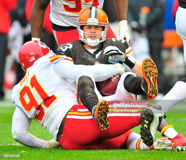 Quarterback Brandon Weeden of the Cleveland Browns is sacked by defensive linemen Tamba Hali of the Kansas City Chiefs during a game with the Kansas...