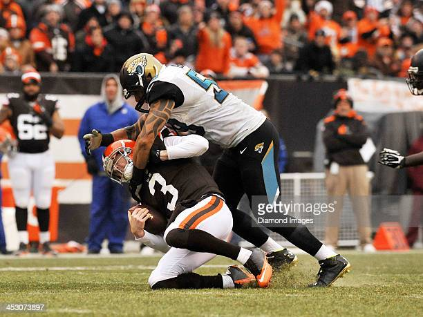 Quarterback Brandon Weeden of the Cleveland Browns is tackled by defensive end Jason Babin of the Jacksonville Jaguars during a game on December 1...