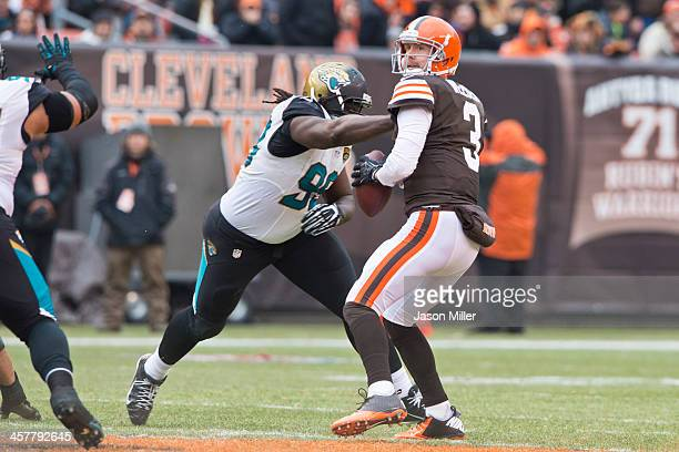 Quarterback Brandon Weeden of the Cleveland Browns looks for a pass while under pressure from defensive tackle Sen'Derrick Marks of the Jacksonville...