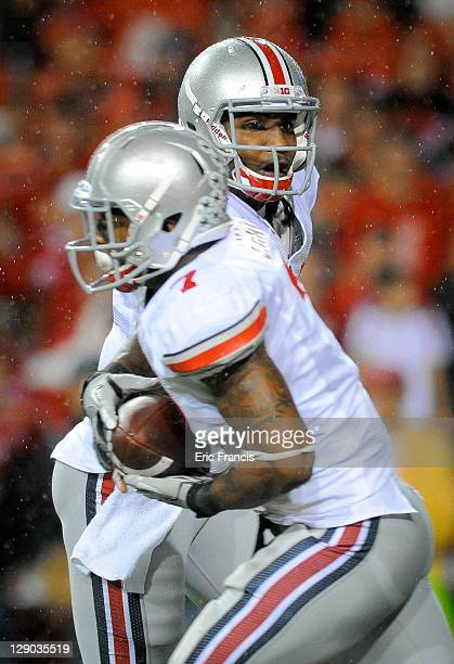 Quarterback Braxton Miller of the Ohio State Buckeyes hands the ball to running back Jordan Hall of the Ohio State Buckeyes during their game against...