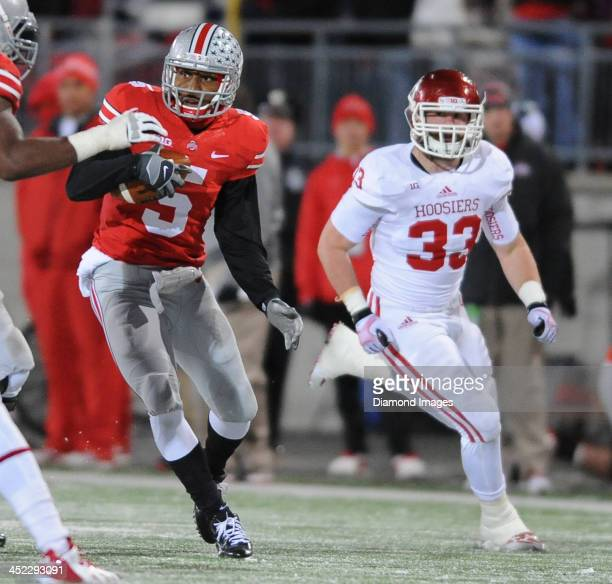 Quarterback Braxton Miller of the Ohio State Buckeyes runs the football away from defensive linemen Zach Shaw of the Indiana Hoosiers during a game...