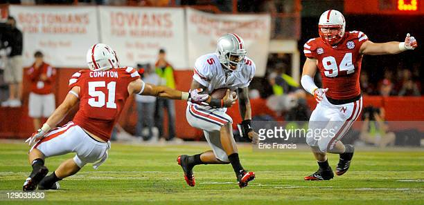 Quarterback Braxton Miller of the Ohio State Buckeyes slips between linebacker Will Compton of the Nebraska Cornhuskers and defensive tackle Jared...