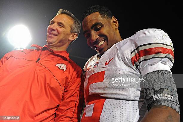 Quarterback Braxton Miller of the Ohio State Buckeyes smiles with head coach Urban Meyer of the Ohio State Buckeyes after defeating the Penn State...