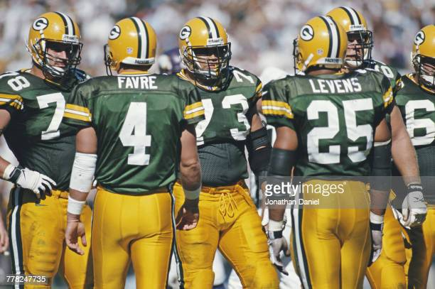 Quarterback Brett Favre and Running Back Dorsey Levens of the Green Bay Packers approach Aaron Taylor and Ross Verba of the offensive line during...