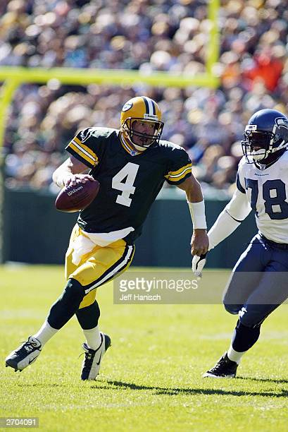 Quarterback Brett Favre of the Green Bay Packers scrambles out of the pocket past defensive end Antonio Cochran of the Seattle Seahawks on October 5...