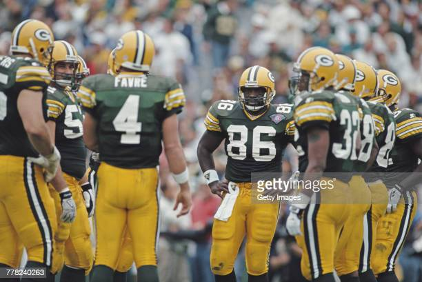 Quarterback Brett Favre of the Green Bay Packers talks to his offensive line in the huddle as Tight End Ed West looks on during the National Football...
