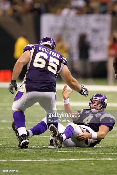 Quarterback Brett Favre of the Minnesota Vikings is helped up by teammate John Sullivan against the New Orleans Saints at Louisiana Superdome on...