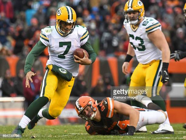 Quarterback Brett Hundley of the Green Bay Packers carries the ball downfield after breaking the tackle of defensive end Carl Nassib of the Cleveland...