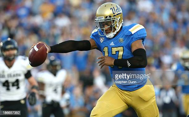Quarterback Brett Hundley of the UCLA Bruins holds out the ball as he scores on an 11 yard touchdown run in the second quarter against the Colorado...